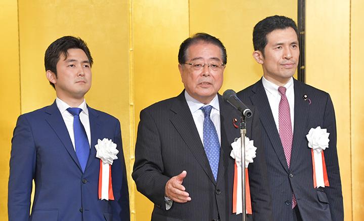 党愛知県本部の懇親の集いであいさつする石田政調会長(中)と安江(左)、新妻の両氏=1日 名古屋市