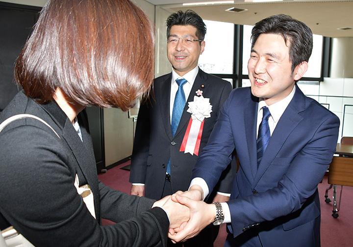 国政報告会で参加者と握手を交わす(右から)安江氏と、里見氏=24日 愛知・岡崎市