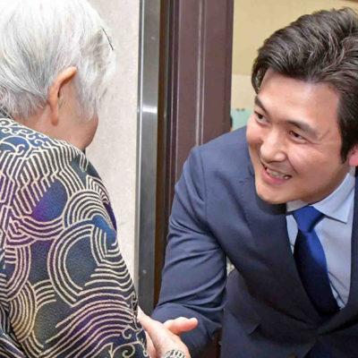 高齢者と固い握手を交わす安江