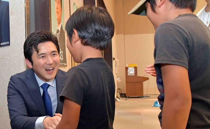 国政報告会で子どもと握手する安江