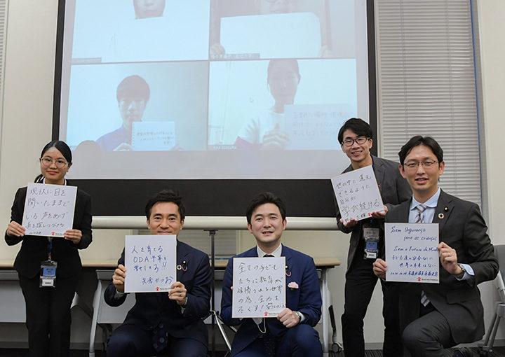 国際貢献への決意をつづった色紙を手に大学生と語り合う矢倉委員長(左から2人目)ら=14日 参院議員会館