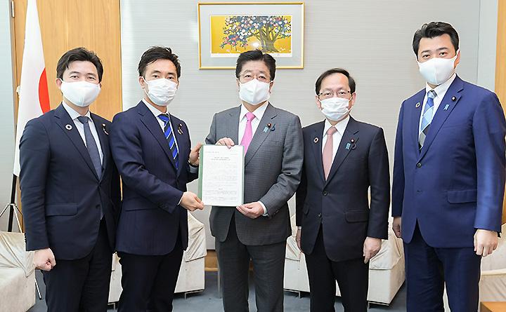 加藤官房長官(中央)に提言する矢倉委員長(左隣)と竹内政調会長(右から2人目)ら=25日 首相官邸